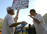 A McCain supporter and an Obama supporter have a heated exchange as people lline up to see...