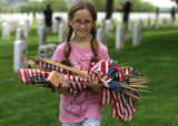 Jordan Abeyta  (cq), 10, has an arm full of American flags to place at graves, Friday morning, May...