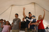 DM1062  Derek and Kara Donahoe raise their hands in praise as they attend an outdoor church...