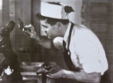 EJ083 An old photograph of Wayne Bortz, working in a chocolate bunny factory.  He's the father of...