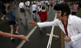 DM1801  Dressed as Elvis, Peter Szameitat, 27, encourages runners in the Boulder Bolder as the...