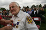 MJM009 Pearl Harbor survivor, Jim Doyle (cq),84, of Lakewood, Colo. gets help attaching his medals...
