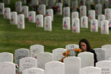 MJM237  Pauline Galvan (cq), of Denver, Colo. places flowers on the grave of her grandfather,...