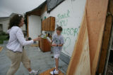 "Sheila Bowman and son Brady Bowman spray paint ""thank you windsor' on the wall of her former..."