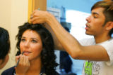 EJ315 Broncos cheerleader Erica Golding gets her makeup done by Angel Garcia, left, and hair done...