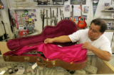 "Salesman Tony Cantu puts away a replica of B.B. Kings guitar ""Lucille"" for $1199.95 at..."
