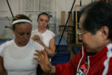 US Synchronized swimmer Janet Culp, center, and teammate Kim Probst receive balance coaching using...