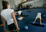 US Synchronized swimmer Janet Culp (back, left) and teammates do stretches at the Circus Center...