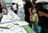 ({seqn)} Cecilia Medina gathers information with her daughter, Ashley, 5, at a Denver Housing Fair...