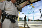 (at left) Richard A Kellet (cq), and RTD security officer waits for a train to board at the Pepsi...
