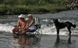 Becky Hesser (cq), right, and friend John Bell (cq), sit in the South Platte River, below...