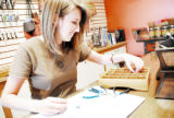 Molly Carlson picks out beads for a set of earrings she's preparing to make at Beadniks, 9325...
