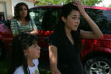 Carolina Valencia, 16, (cq) pulls her hair back outside of her mothers home Monday afternoon....