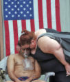 A resident of the Airways Hotel is comforted by a friend as he waits to be transported to the...