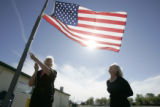 Pat Stoops (cq), left, and JoDene Ireland (cq), right, put their flag at half-mast in front of...