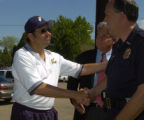 Luis Romero thanks Denver D.A. Mitch Morrisey, and Denver Police Chief Gerry Whitman, left to...