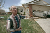 BG0246 Bob Henderson points at the garage where he hid under a Ford Explorer when the tornado hit...