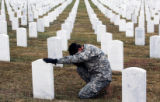 (118) Staff Sgt. Chris Rogers (cq), places his hand on the gravestone of his uncle, Vietnam...