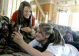 Cousins Matti Sperry, 13 and Kelley Sperry take turns taking pictures of each other on their...