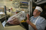 Nick Lonardo weighs a large bag of sausage for a customer Carbone's Sausage Market and Deli on...