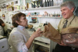 Rose Carbone, left, gives customer Len Skovira of Parker a small bag of candy-coated almonds,...