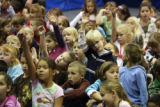 Children hold up hands for questions to Yohannes Gebregeorgis (cq)  at Arrowwood Elementary in...