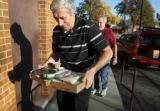 L to R: Volunteers Chris Michalik (cq) and Jim Scharfenberg (cq) carry food into the Arvada...