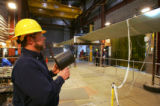 (050) Darren Rahn, does a visual inspection of a wind blade during a fatigue test at the National...