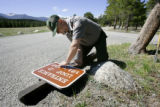 Rocky Mountain National Park Ranger George Weaklim (cq) of Estes Park attends to a sign in need of...