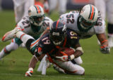 (CS1694) Eddi Royal is tackled by Channing Crowder and Andre Goodman in the third quarter of the...