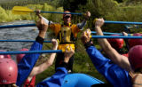 Billy Mattison, yellow, instructs a group of rafters on how to hold a paddle before a river tripe...