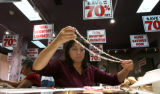 Tammy Vogt (cq) works on pricing jewelry for a going out of business sale, Tuesday morning,...