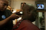 Nicole Melon (cq), a hair stylist at House of Hair in Park Hill, shaves customer Agyemang Gyimah's...