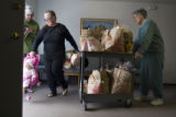 (116) Ella Baldwin, 61, center, of Aurora, pulls a cart loaded with groceries while she picks up...