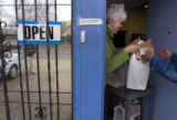 (243) Aurora Interchurch Task Force Executive Director Judy Barrow hands over a bag of grocecries...