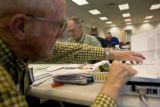Peter Braaksma (cq) (left) sets a ballot aside while Herb Fletcher (cq) tears stubs used for...