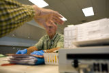 Peter Braaksma (cq) (left) sets a ballot aside while Herb Fletcher (cq) organizes ballots. Both...