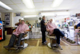 On left, Cliff Hohenstein and Adam Fleckenstein are at Chuck's Barber Shop getting their hair cut...
