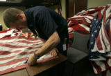 Firefighter Pete Johnson (cq), 26, cuts-up a flag to prepare it to be retired at the West Metro...