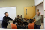Volunteers with the U.S. Department of Veterans Affairs push a cart full of used shoes   at the...