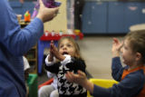 Magdalena Jordon (cq), age 5, and Nathanial Covington (cq) age 5, catch bubbles from teacher...