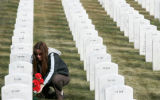 (045) Tavia Heckle (cq), of Lakewood, places flowers at the gravestone of her father-in-law Ed...