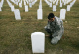 (263) Staff Sgt. Chris Rogers (cq), kneels next to the gravestone of his uncle, Vietnam Veteran...
