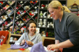 (0043) Jamie Brenner, left, laughs as Whitney Chotin helps her knit a sweater vest at i Love...