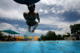 (PG15648)  Alejandra Acosta, 9, slides into La Alma city pool in Denver, Colo., on Sunday, June...