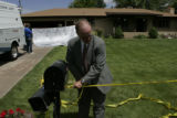 Adams County Sheriff's captain Fred Stoll (cq) ties crime scene tape around a mailbox Sunday...