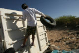 MJM263 Jacob Fierro (cq), 13, throws an old tire into a dumpster during a cleanup planned by the...