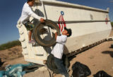 MJM279  Jacob Fierro (cq), 13, left, takes an old tire from Fernando Ramirez (cq), 10, center,...