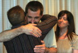 Brandon Trask left, hugs Tom Koldeway as Tom's wife Trish Koldeway looks on after announcing a...