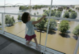 Valentine Chenus, 6, of Davenport, walks on the Sky Walk above the flooded areas of downtown from...